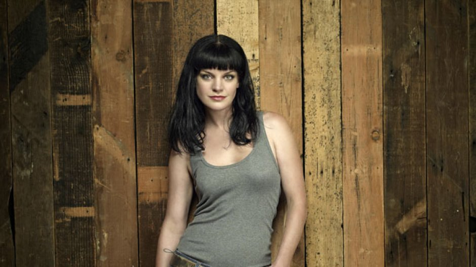 Pauley Perrette is wearing a grey t-shirt and is leaning on the wall