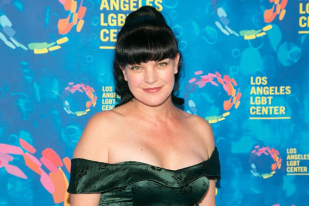 Pauley Perrette is wearing a black shoulder-of t-shirt
