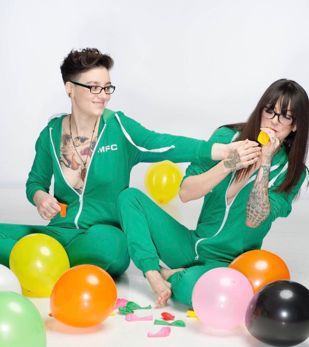 Olivia Black shares a joyous time with her lesbian wife, Maria Plaza. The two are sitting next to each other wearing a same green attire. They are surrounded by balloons. Olivia is trying to blow up the balloon while her wife is holding her hands.