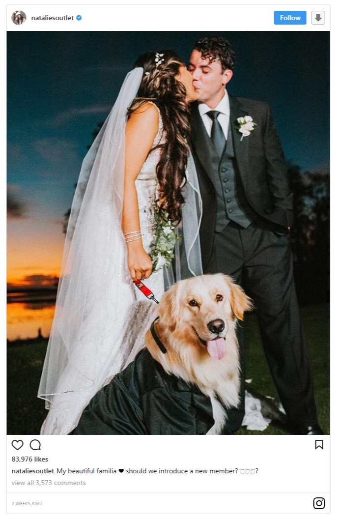 Natalie Outlet sharing a snap with her husband, Dennis on Instagram. She is holding dog's strap with her right hand and is kissing her husband. Natalie and her husband are in their wedding dresses.