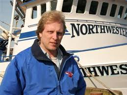Sig HAnsen is wearing a blue jacket and is standing in front of a ship