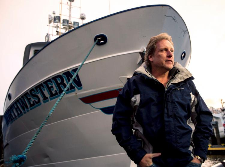 Sig Hansen is standing in front of the boat