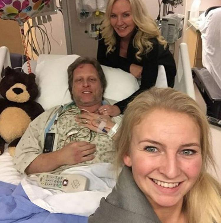 Sig Hansen in hospital recovering after a massive heart attack. He is lying in bed next to his wife and daughter, Mandy, who is taking the picture.
