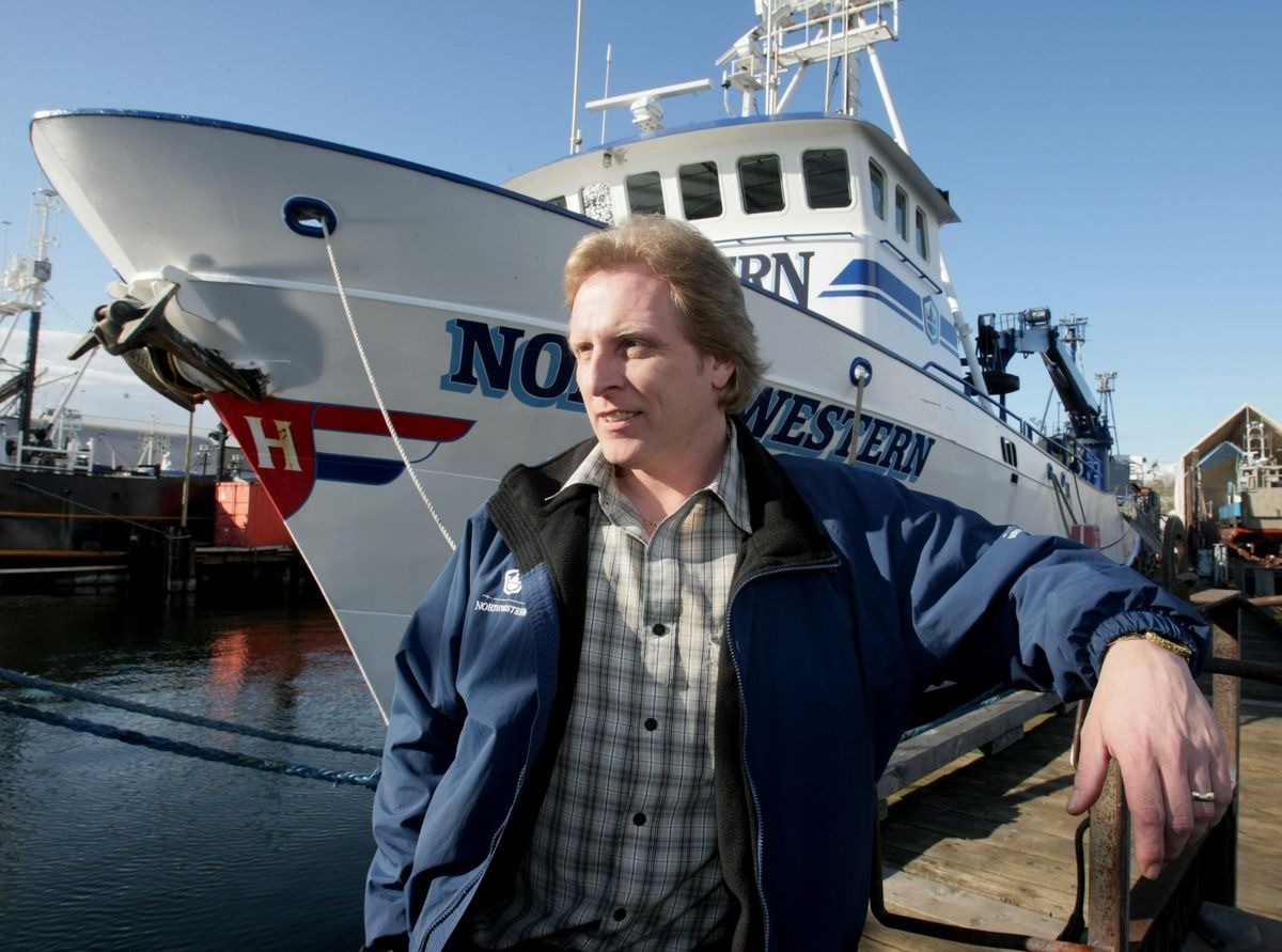 Sig Hansen infront of his ship, Northwestern. The ship is docked at port. Sig poses for the camera as he looks away from it. He is wearing a blue jacket.