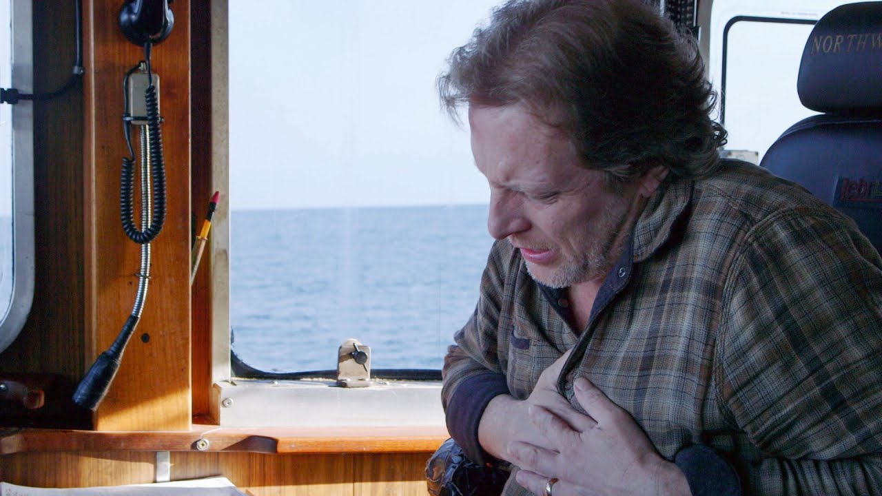 Sig Hansen holding his left chest due to pain in a boat