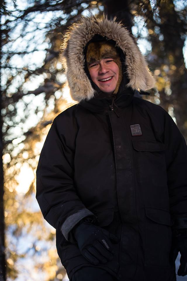 Joey Zuray in furry head cap and black jacket with a big smile on his face