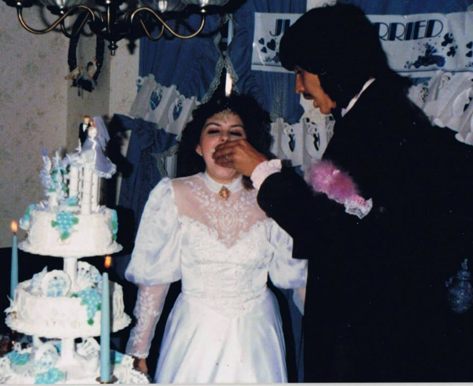Jerry Monza is nourishing a cake to his wife. Both the couple are on a wedding dress. Monza is wearing a black suit while his wife is wearing a white wedding dress. Besides them rests a massive cake.