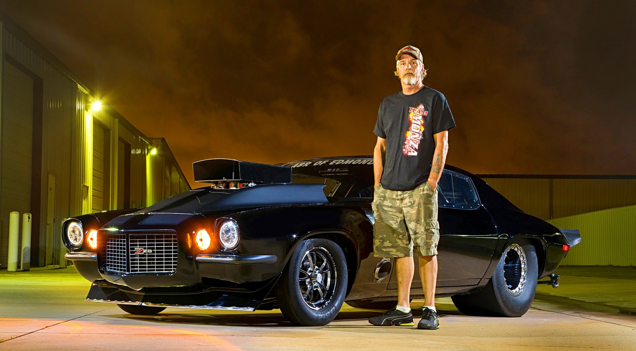 Jerry Monza is standing in an outdoor infront of his 1972 Chevrolet Camaro Rally Sports also named as the Sinister Split Bumper. He is wearing a black t-shirt, a camo half pant and a cap. He has tucked both his hand inside his pocket. Jerry is looking straight in the camera.