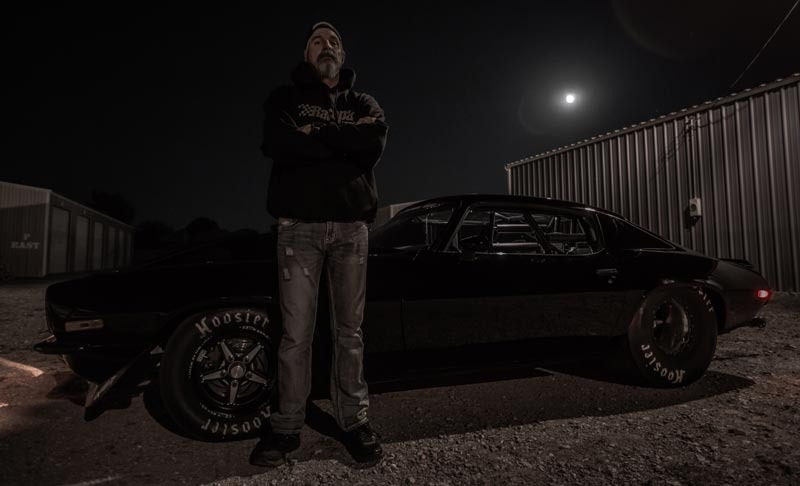 Jerry Monza is standing outdoor in the night. Jerry is standing straight with his arms crossed. He is wearing a black hoodie. In the background stays his Sinister Split Bumper.