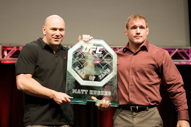 Dana White and Matt Hughes posing for a picture holding the UFC hall of fame trophy of Matt Hughes