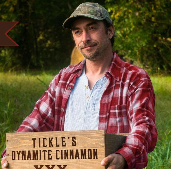 """Steven Ray Tickle is holding a wooden box with a imprint """"TICKLE'S DYNAMITE CINNAMON."""" He is wearing a red-check shirt while looking away from the camera. He is a star of TV show, Moonshiners and Tickle."""