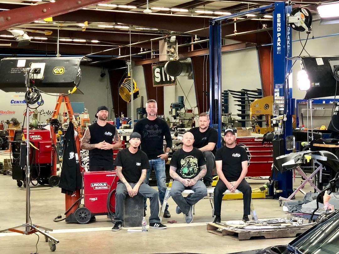 Jason Aker along with Gas Monkey Garage's team members are posing for a photo wearing GMG's t-shirt.