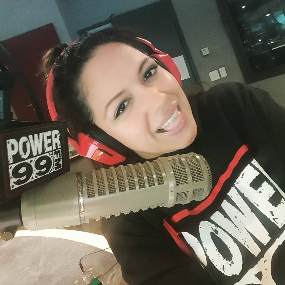 Mina Llona is at the radio station of Power99. Before her stands a silver mic. She is wearing a black hoodie. She is wearing a red headphone. She is looking at the  camera pulling her tongue out.