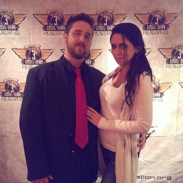 Kris Ford and his wife, Stephanie Ford are posing for the camera. Kris is wrapping his hands on Stephanie's waist.