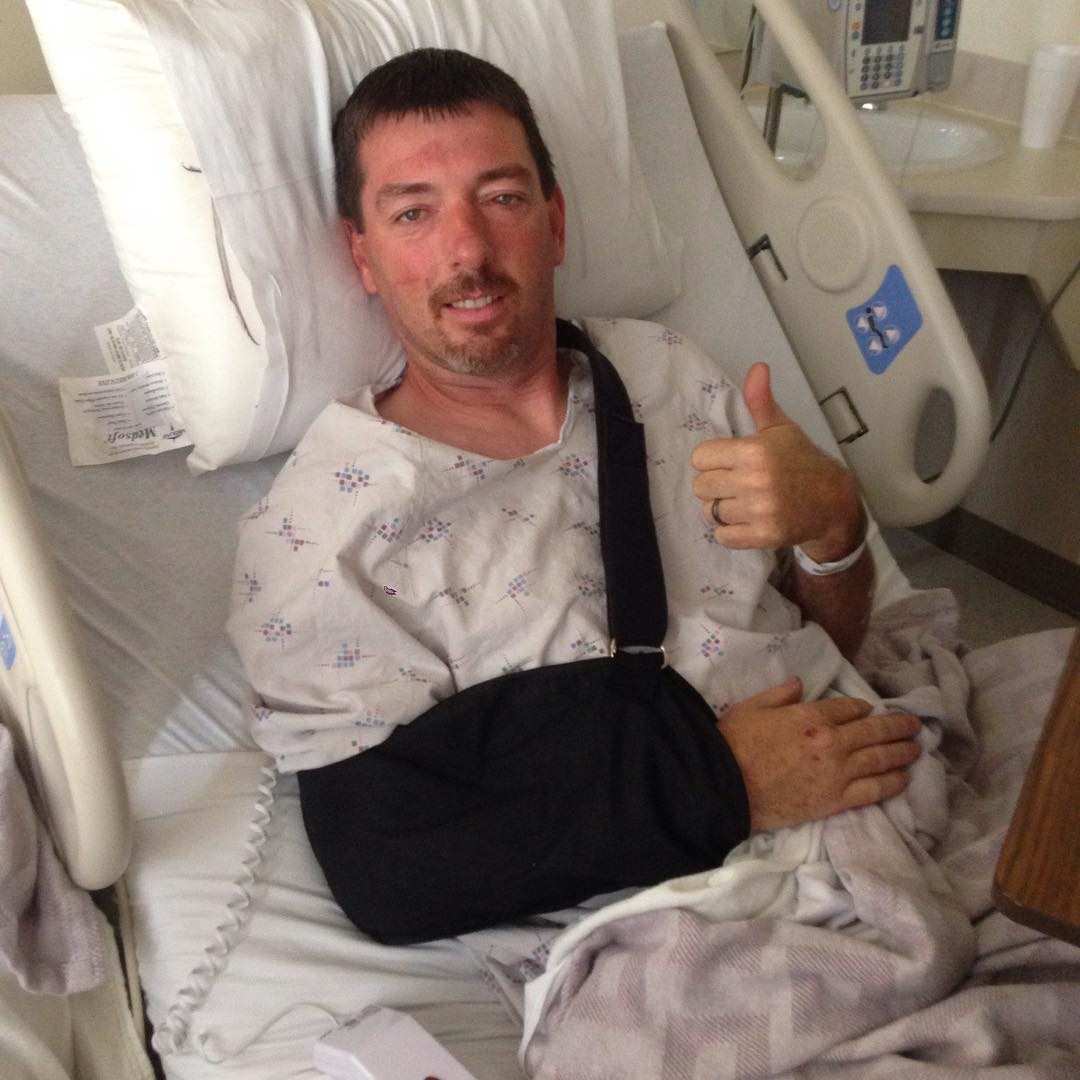 Daddy Dave is leaning down on hospital bed
