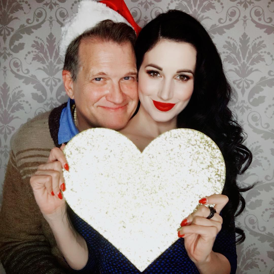 Amie Harwick is holding a love sign of glittered paper in her hand showing to the camera while Drew Carey is hugging her from backward wearing a Christmas hat.
