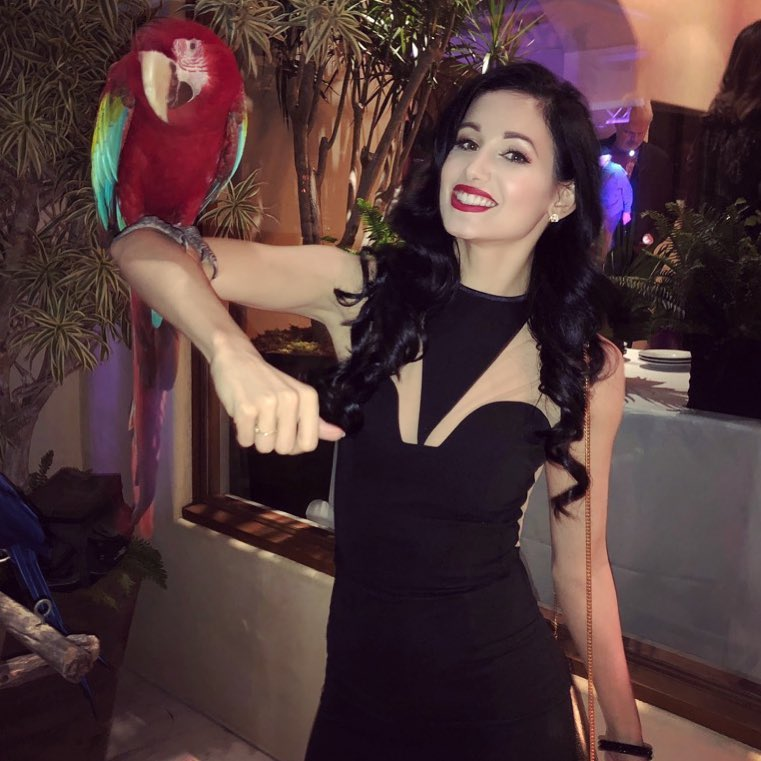 Amie Harwick is smiling towards the camera. She is holding a parrot on her right elbow. She looks dashing in her black slim fit attire.