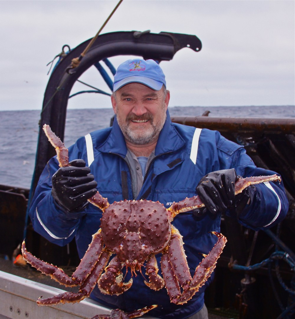 Captain Keith Colburn catching a crab on his hands with a smile on his face