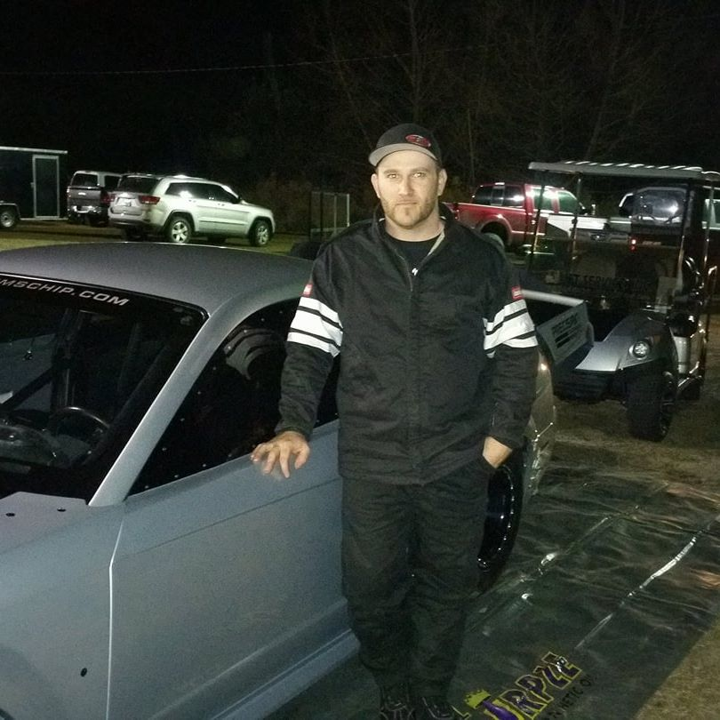 Brandon Smith stands next to his car