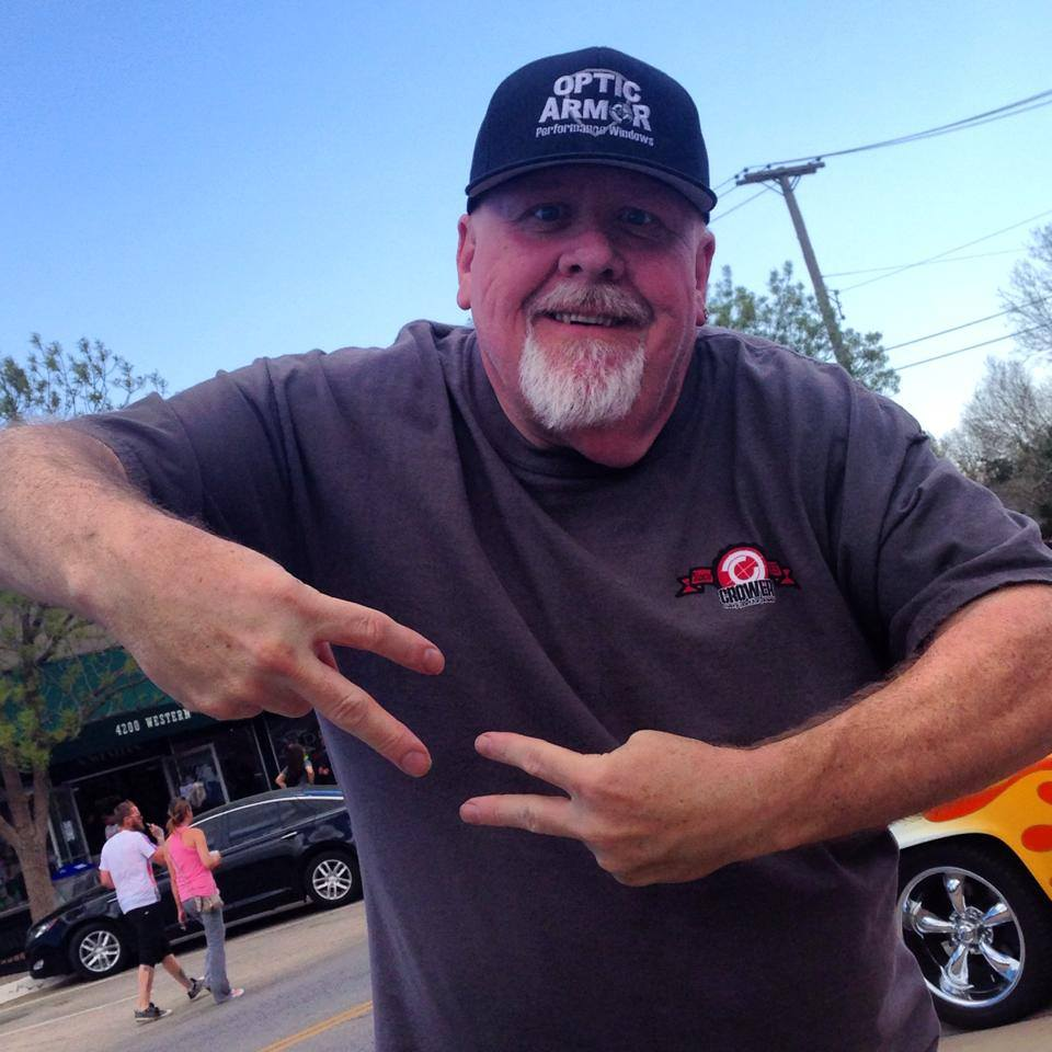 Wayne Varley poses in the outdoor. He is wearing a grey T-shirt and a black cap.