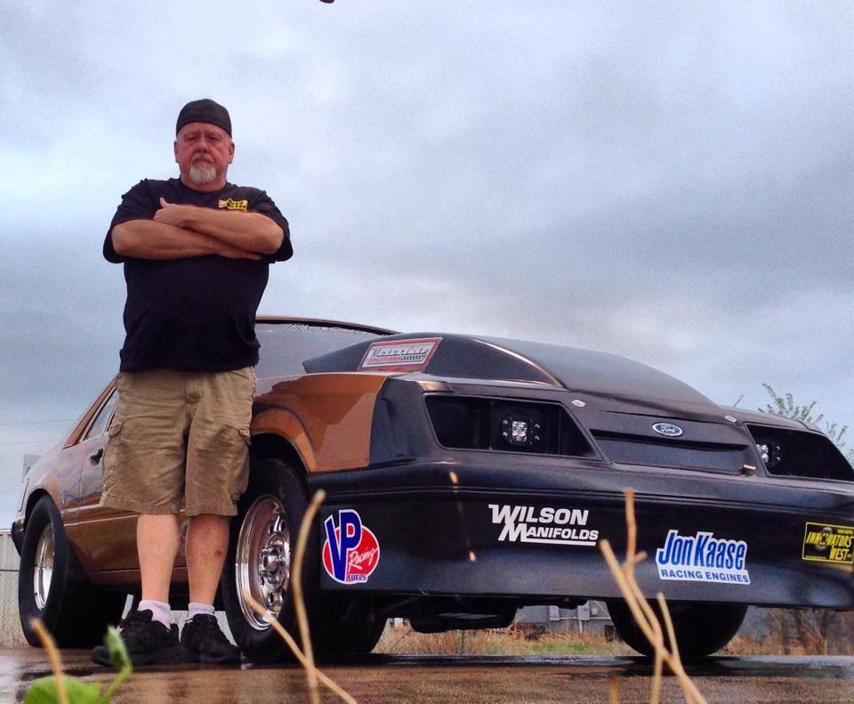 Wayne Varley stands next to The Gold Car.
