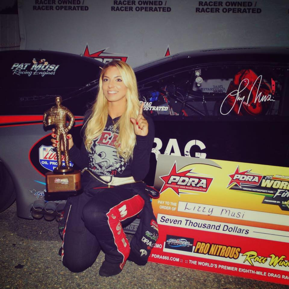 Lizzy Musi posing with a trophy of Pro Nitrous National event