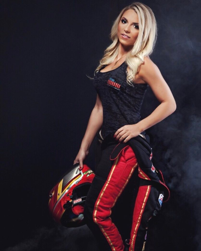 Lizzy Musi poses in the driving suit, holding a red helmet.