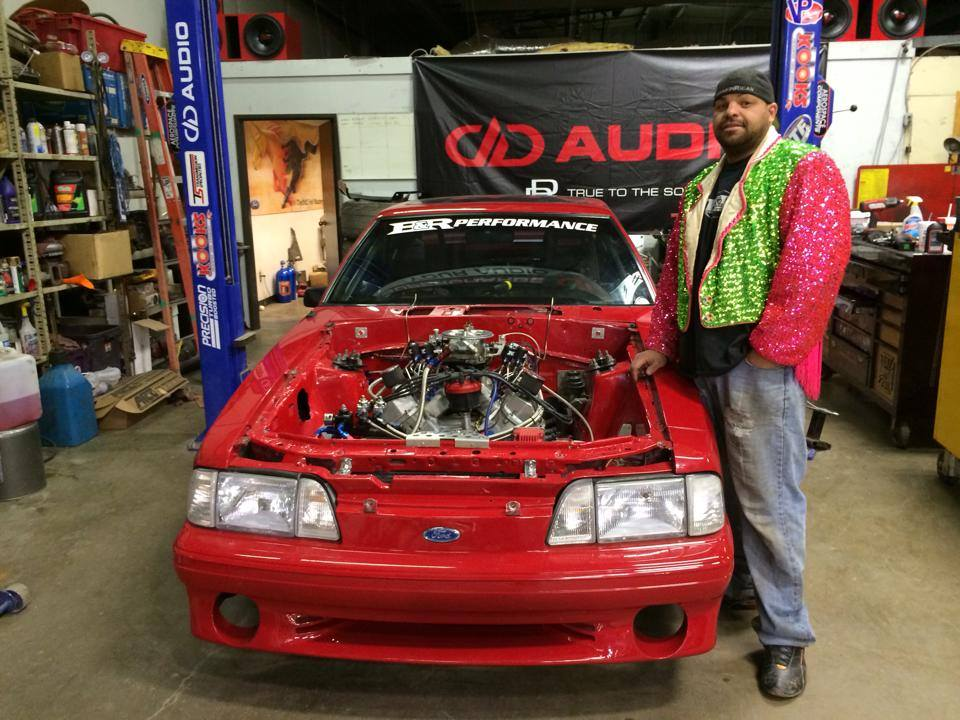 """Jose """"Freakin Rican"""" Rivera is standing next to 1991 Ford Mustang aka Freak of Nature in B&R performance shop."""