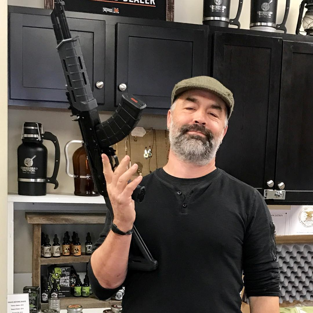 Jason Knight is holding a gun in his right hand