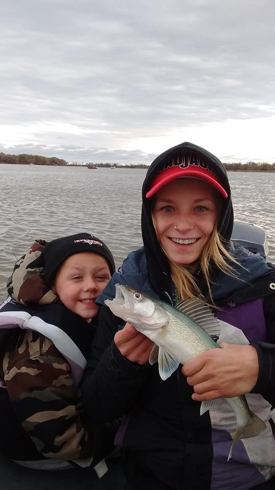 Stephanie Custance is carrying a fish and her son is standing by her side