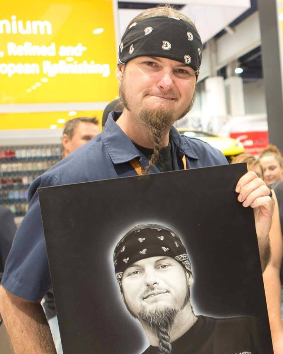 Ryan Evans holding his portrait artwork.