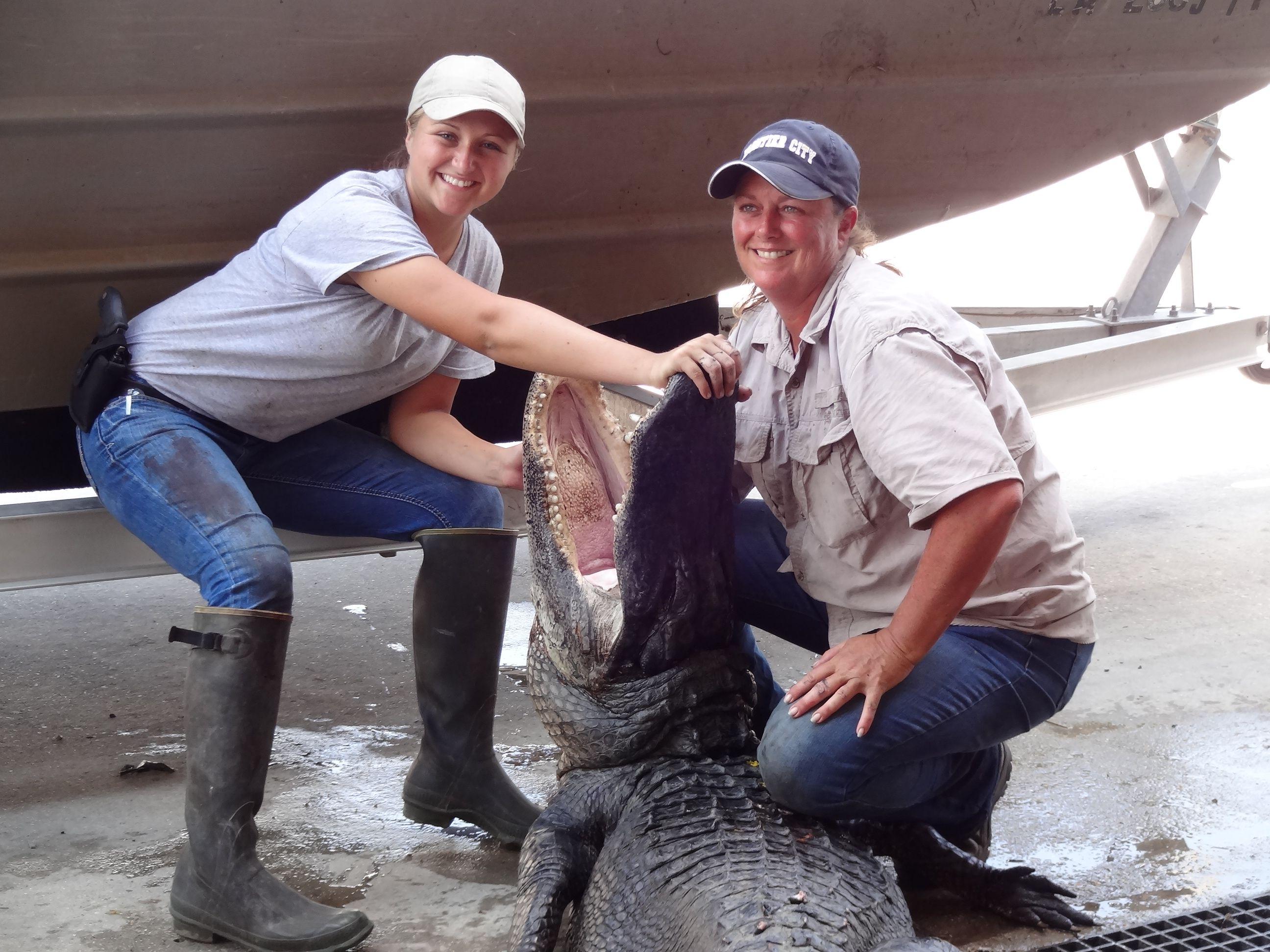 Liz Cavalier and his daughter, Jessica holding a massive alligator.