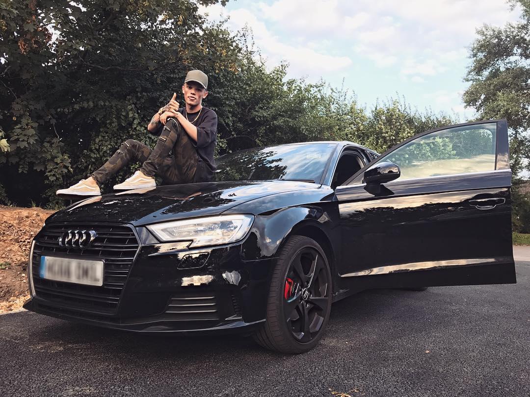 Charlie Lenehan poses on the hood of his shiny black Audi.