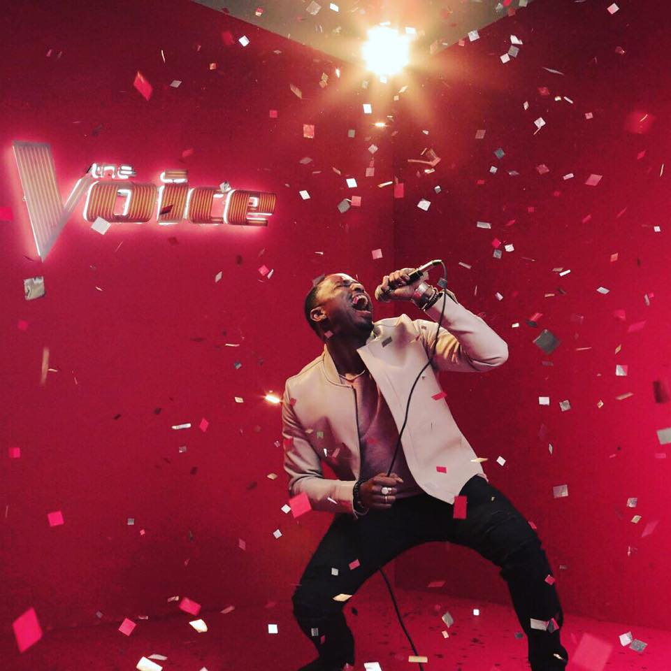 Rayshun LaMarr holding a mike in his hand while performing on The Voice