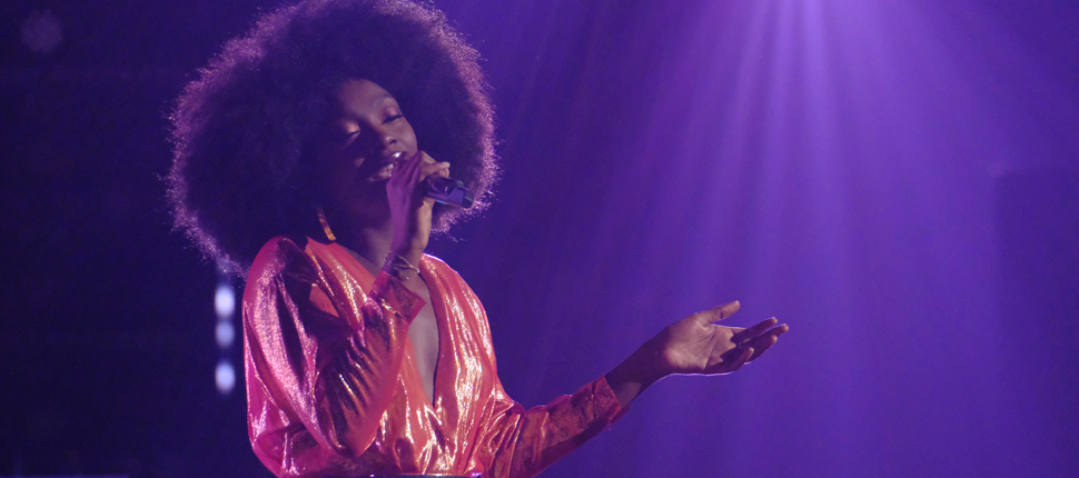 Christiana Danielle is singing as she holds a mike in her hand