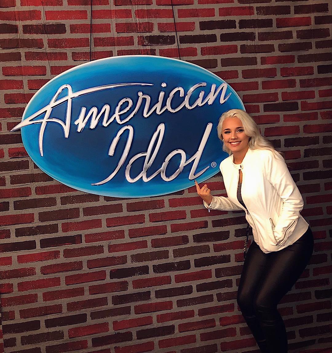 Gabby Barrett point out the American Idol logo