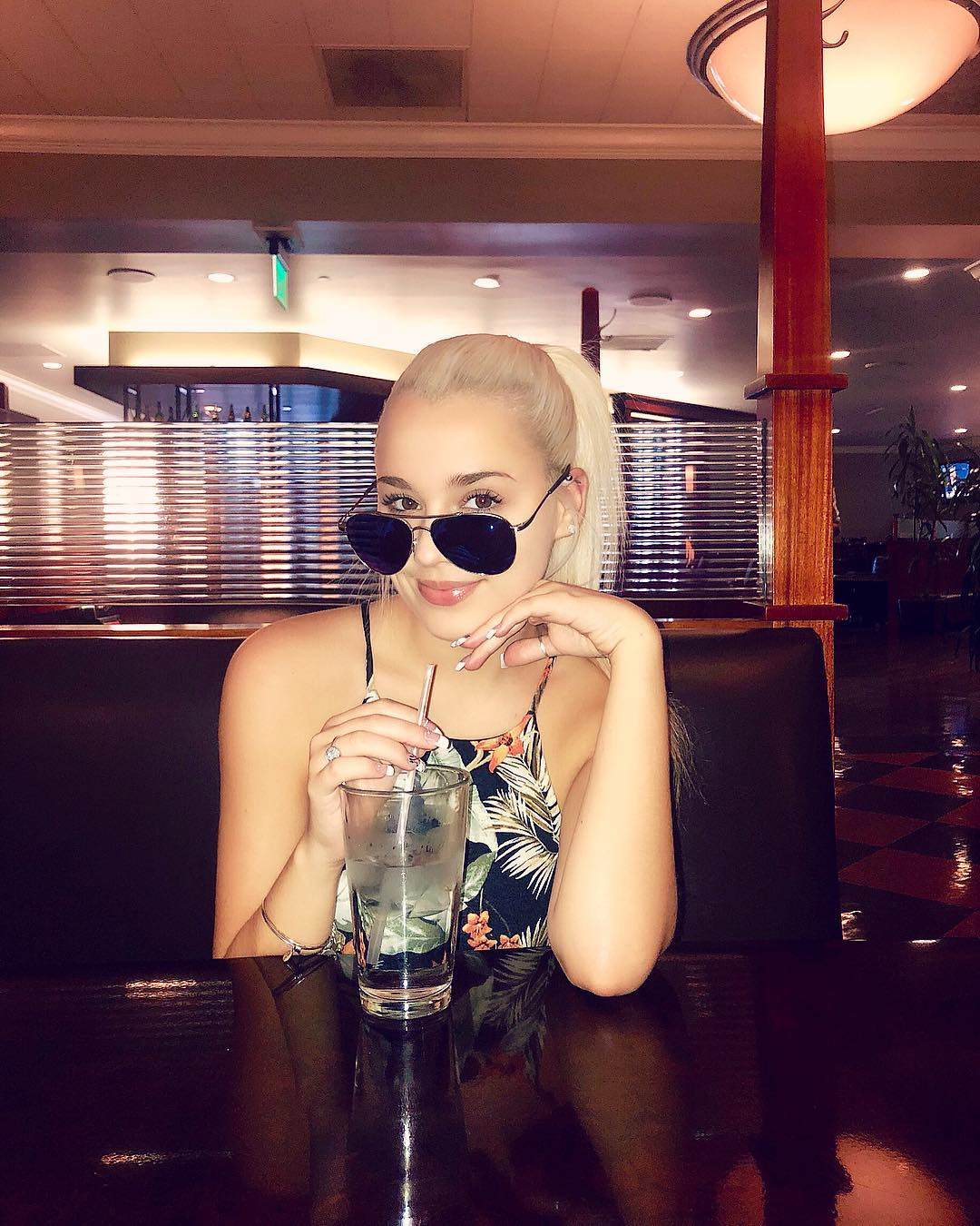 Gabby Barrett holds a straw with her right hand