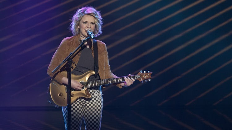 Maddie Poppe is on the stage with golden guitar