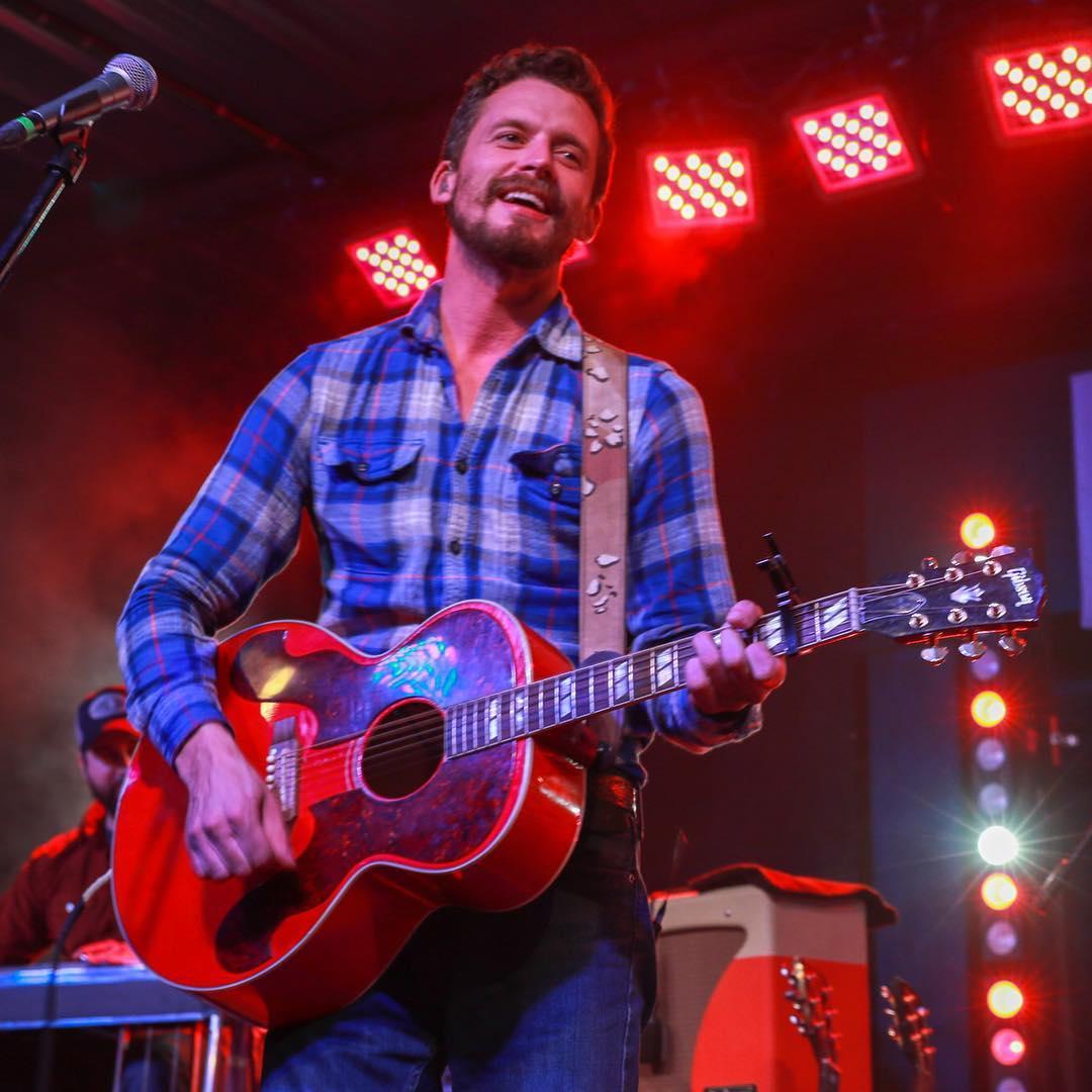 Evan Felker is holding a guitar on his hand as he sings