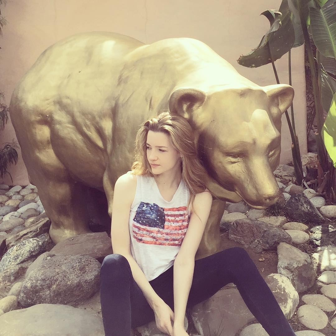 Talulah Riley is wearing a white t-shirt and sitting in front of a bear statue