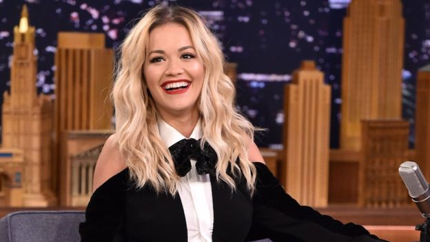 Rita Ora has a blonde hair and is wearing a black and white shouder off t-shirt