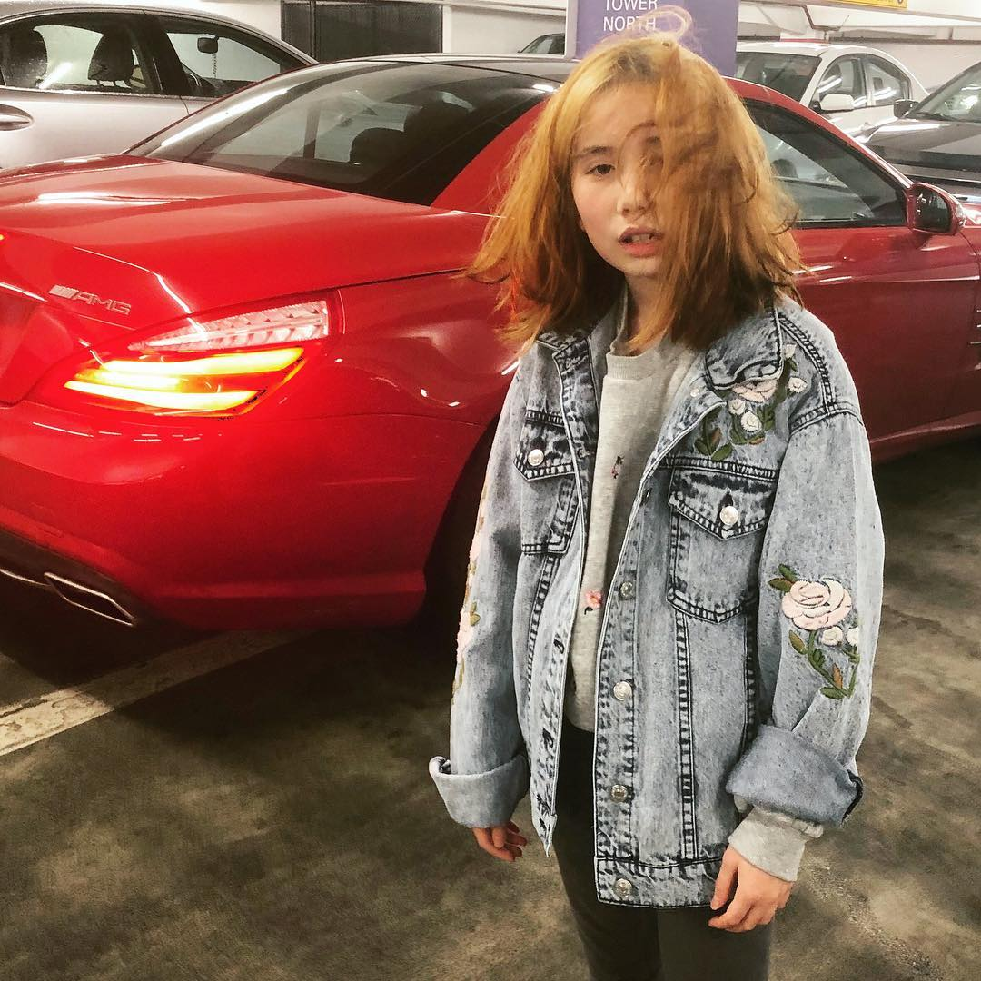 Lil Tay is wearing a jeans jacket and has her hair all messed up