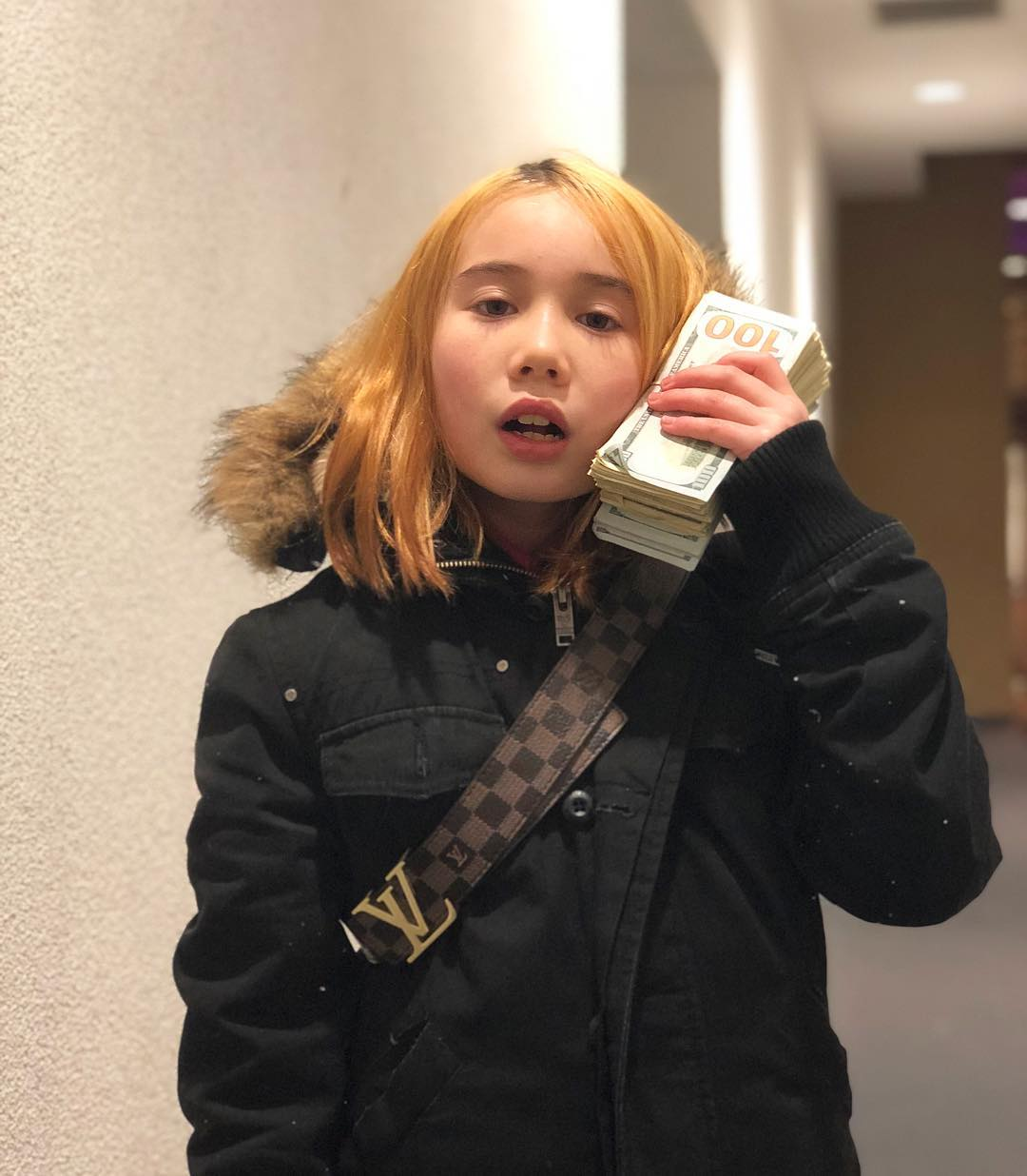 Lil Tay is holding a bunch of money and is keeping it near her hair