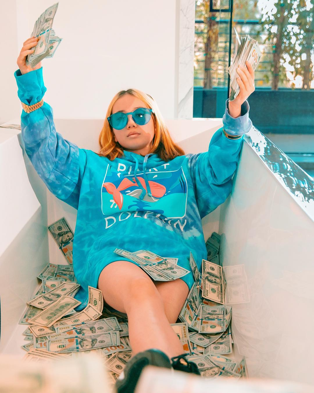 Lil Tay is lying on a tub with money all over her