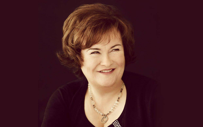 Susan Boyle smiling wearing a black dress