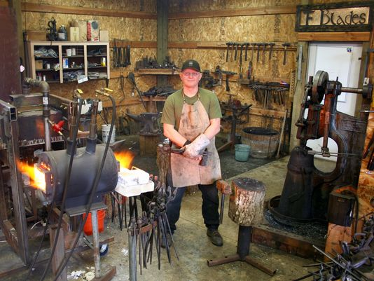 Tony Fretters is standing in his workroom with a tool in his hand