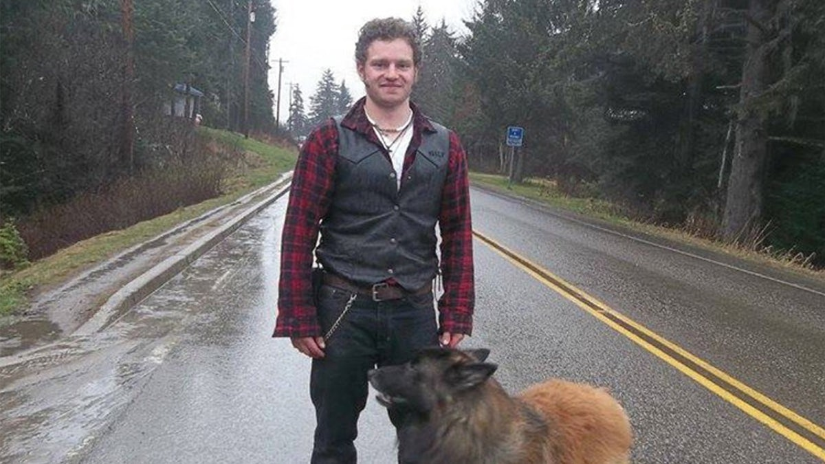 Gabe brown standing in the middle of a road with his dog