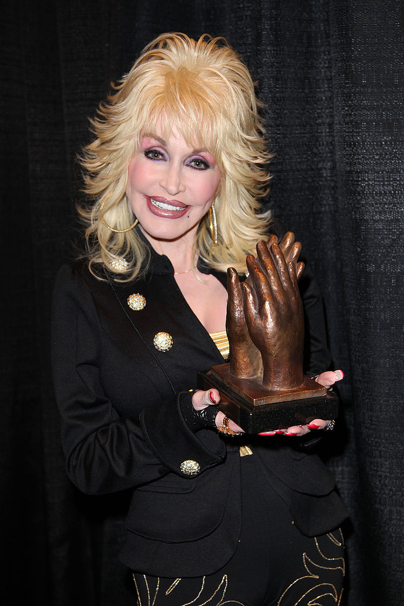 Dolly Parton holding an award. The award shows two hands clapping