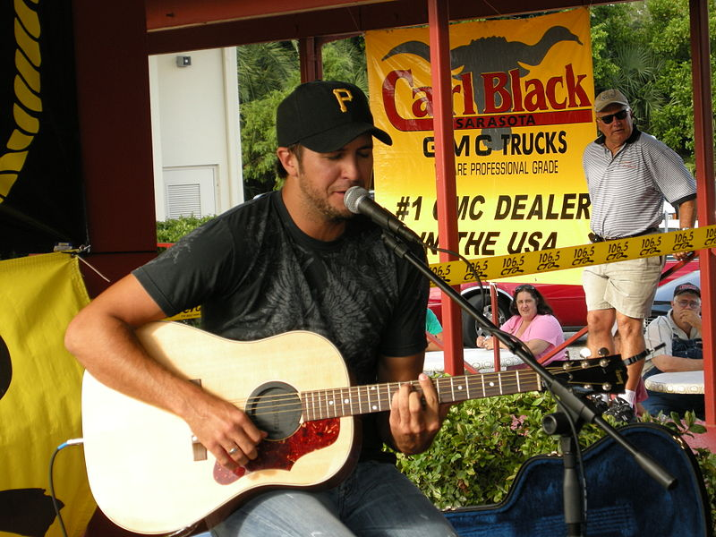 Luke Bryan singing song and playing guitar in front of the people