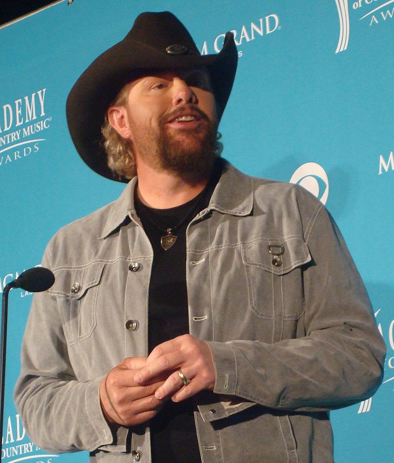 Toby Keith interacting with people. He is wearing a black hat and there is a microphone in front of him.
